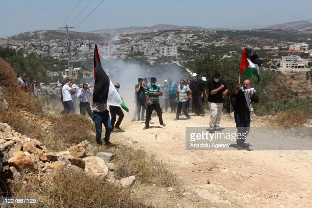 Palestinian demonstrators are seen among tear gas smoke launch by Israeli forces following their intervention in a protest against the illegal Jewish...