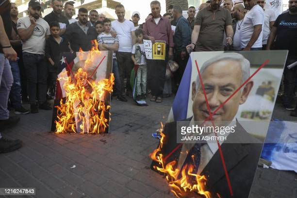 Palestinian demonstrators burn pictures of US President Donald Trump and Israeli Prime Minister Benjamin Netanyahu during a demonstration against the...