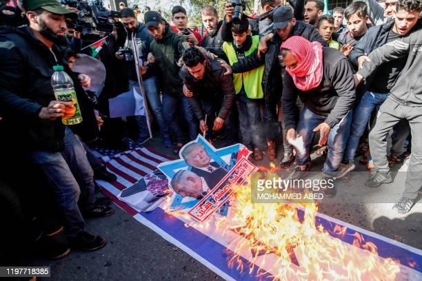"Palestinian demonstrators burn portraits of US President Donald Trump and Israeli Prime Minister Benjamin Netanyahu with the slogan in Arabic ""Down..."