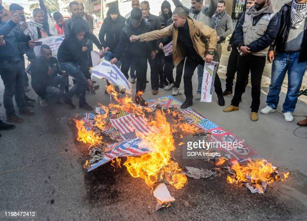 Palestinian demonstrators burn the illustrations of the British Union flag, the Israeli flag, and an American flag during a protest against the...