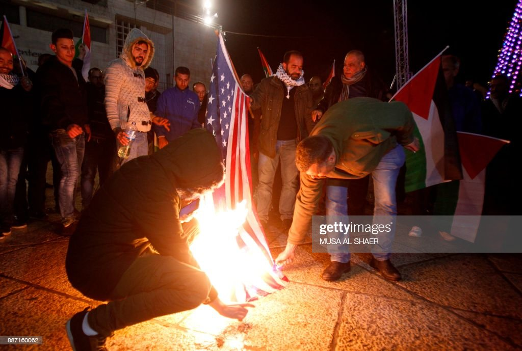 Palestinian demonstrators burn the US flag in Bethlehem's Manger Square in protest to the declaration of the US president declaring Jerusalem as Israel's capital on December 6, 2017. Abbas said the United States can no longer play the role of peace broker after Donald Trump's decision on Wednesday to recognise Jerusalem as Israel's capital. / AFP PHOTO / Musa AL