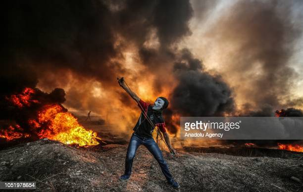 Palestinian demonstrators burn tires and throw rocks with slingshots after Israeli forces' intervention during the Great March of Return...