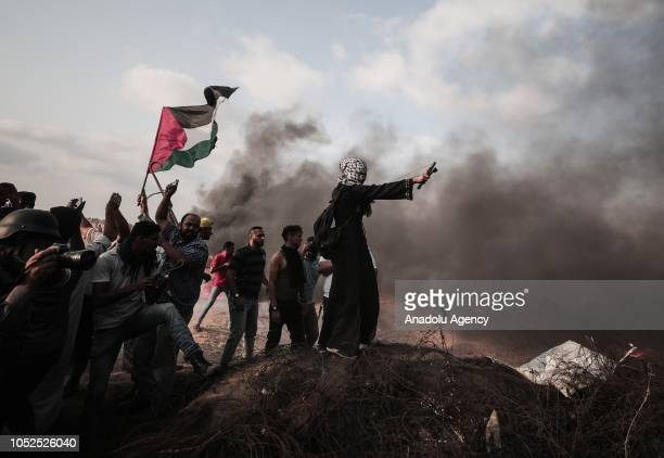 Palestinian demonstrators burn tires and throw rocks with slingshots in response to Israeli soldiers' intervention during the Great March of Return...