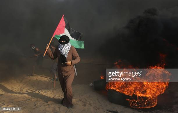 Palestinian demonstrators burn tires as Israeli forces use tear gas to disperse them during the Great March of Return demonstration near IsraelGaza...