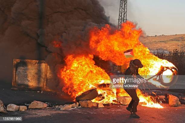 Palestinian demonstrators burn tires during a protest against the tension in Jerusalem and the Israeli-Gaza fighting, on May 17, 2021 in the occupied...