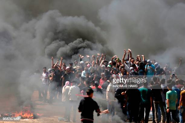 TOPSHOT Palestinian demonstrators burn tyres near the GazaIsrael border east of Gaza City as Palestinians readied for protests over the inauguration...