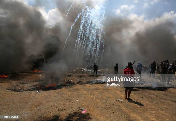 Palestinian demonstrators burn tyres near the GazaIsrael border east of Gaza City as Palestinians readied for protests over the inauguration of the...