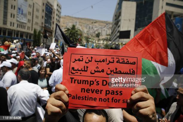 Palestinian demonstrators carry a banner and a national flag during a protest against the US-sponsored Middle East economic conference that opens...