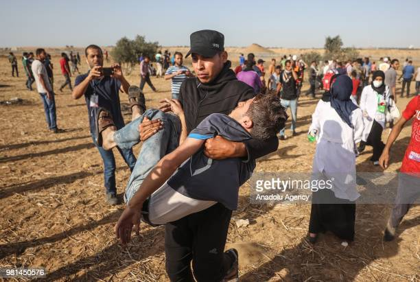Palestinian demonstrators carry a boy who injured after Israeli security forces' intervention during a demonstration held within the Great March of...