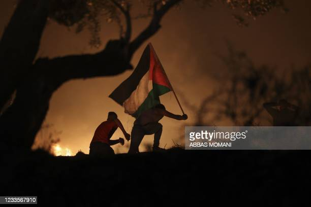 Palestinian demonstrators carry a flag as they gather during the night clashes following a demonstration against Israeli settlements in the village...