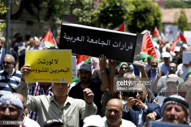 Palestinian demonstrators carry a makeshift coffin with the inscription the decisions of the Arab League during a protest against the USled Peace to...