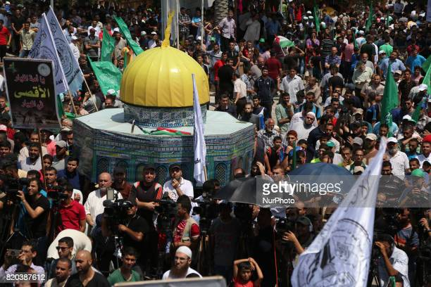 Palestinian demonstrators carry a model of the Dome of the Rock mosque in Gaza City on July 22 as they protest against new Israeli security measures...