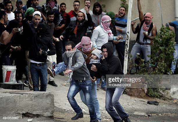 Palestinian demonstrators carry an injured comrade during clashes with Israeli security forces in the West Bank city of Hebron on October 30 2015...