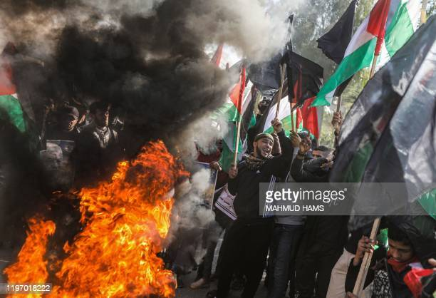 Palestinian demonstrators chant slogans and wave Palestinian flags as they stand by flaming tyres during a protest against US President Donald...