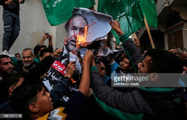 TOPSHOT Palestinian demonstrators chant slogans before burning pictures of Israeli Defence Minister Avigdor Lieberman in front of the house of Ismail...