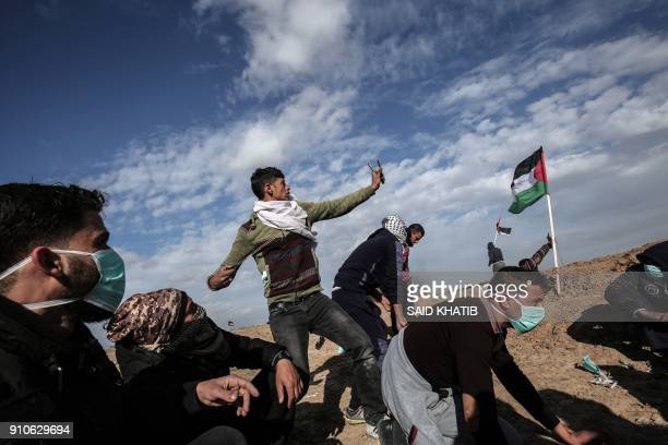 Palestinian demonstrators clash with Israeli forces near the Israel-Gaza border east of the southern Gaza strip city of Khan Yunis on January 26,...