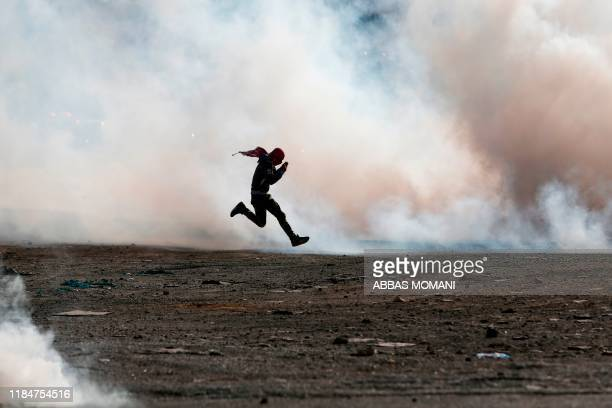 TOPSHOT Palestinian demonstrators clash with Israeli security forces on November 26 in the West Bank city of Ramallah following a demonstration...