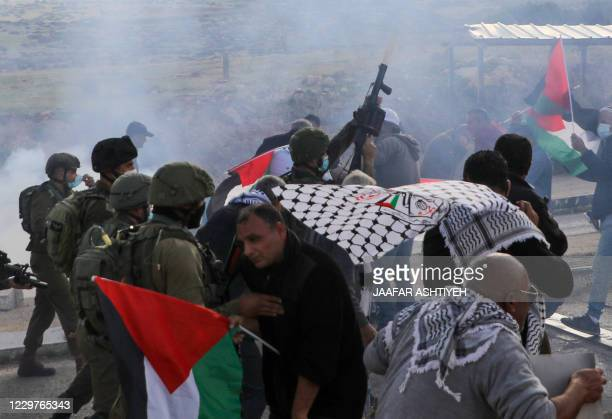 Palestinian demonstrators clash with Israeli soldiers during a protest against Jewish settlements on November 24 in the Jordan Valley in the...
