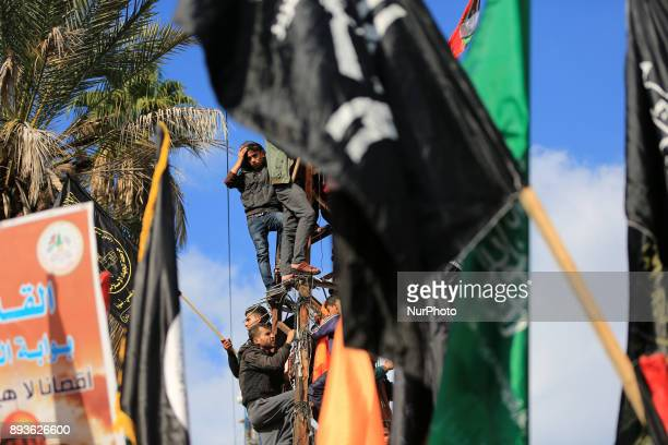 Palestinian demonstrators climb up a pole holding flags during a rally in Gaza City in Gaza Strip on December 15 2017 to protest against US President...