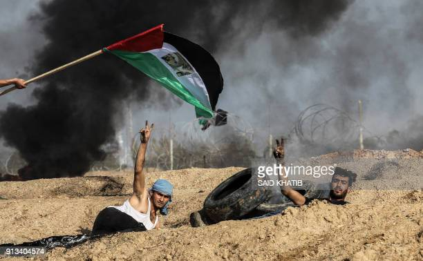Palestinian demonstrators flash the victory gesture as smoke is seen behind them and a Palestinian flag waving above them, during clashes with...
