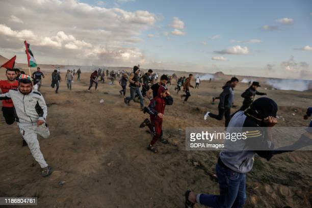Palestinian demonstrators flee from tear gas canisters fired towards them by the Israeli forces amid confrontations during a demonstration along the...