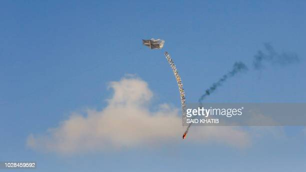 TOPSHOT Palestinian demonstrators fly a kite carrying incendiary materials to set fire to Israeli territory during clashes following a demonstration...
