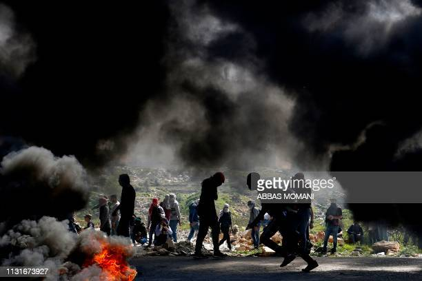 TOPSHOT Palestinian demonstrators from Birzeit University take cover during clashes with Israeli forces in Ramallah near the Jewish settlement of...