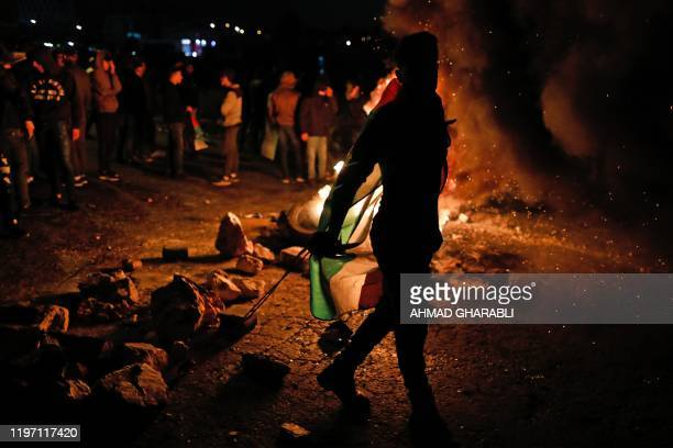 Palestinian demonstrators gather around burning tyres during a demonstration against US President Donald Trump's peace plan proposal on January 28 at...