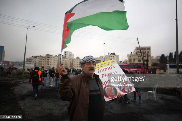 Palestinian demonstrators gathered at Beit El military checkpoint stage a protest against US President Donald Trump's Middle East plan in Ramallah...