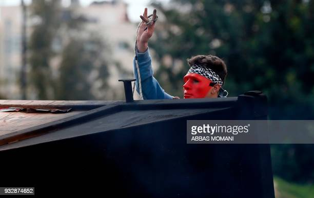 A Palestinian demonstrators gestures with the middle finger towards Israeli security forces during clashes following a demonstration in the West Bank...