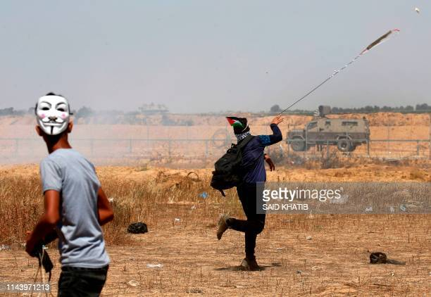 Palestinian demonstrators hurl rocks towards Israeli soldiers east of Khan Yunis in the southern Gaza Strip on May 15 during a protest marking 71th...