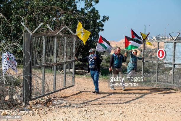 Palestinian demonstrators open a gate, part of an Israeli barrier, in the village of Kafr Thulth, east of Qalqilya in the occupied West Bank on...