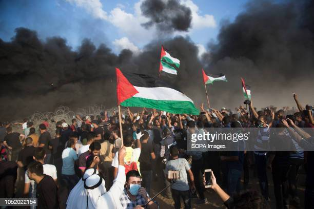 Palestinian demonstrators raise the flag of Palestine during the protest Palestinians clash with Israeli forces during a protest calling for lifting...