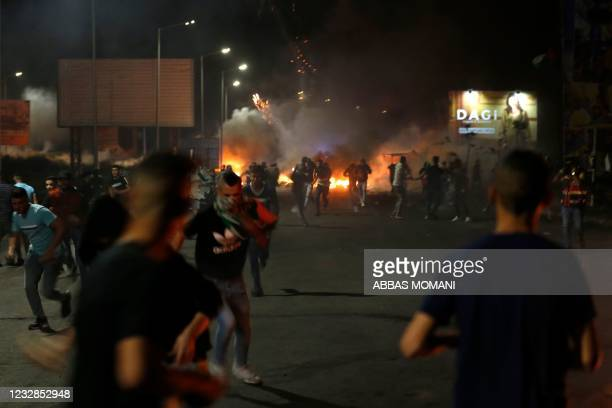 Palestinian demonstrators run away from the gas fired by Israeli soldiers during an anti-Israel demonstration over tensions in Jerusalem near the...