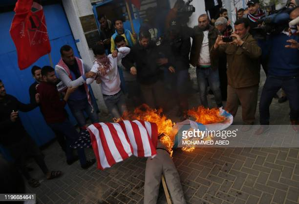 Palestinian demonstrators set an effigy depicting US President Donald Trump on fire during a protest against his Middle East peace plan, on January...