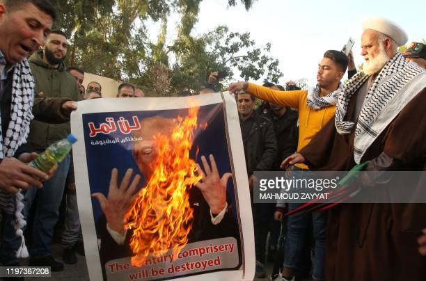 Palestinian demonstrators set an image of US President Donald Trump on fire during a protest in the Rashidiyah camp near Lebanon's southern port city...