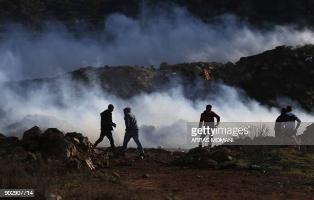 TOPSHOT Palestinian demonstrators stand amidst tear gas smoke launched by Israeli forces during a protest against the US' decision to recognise...