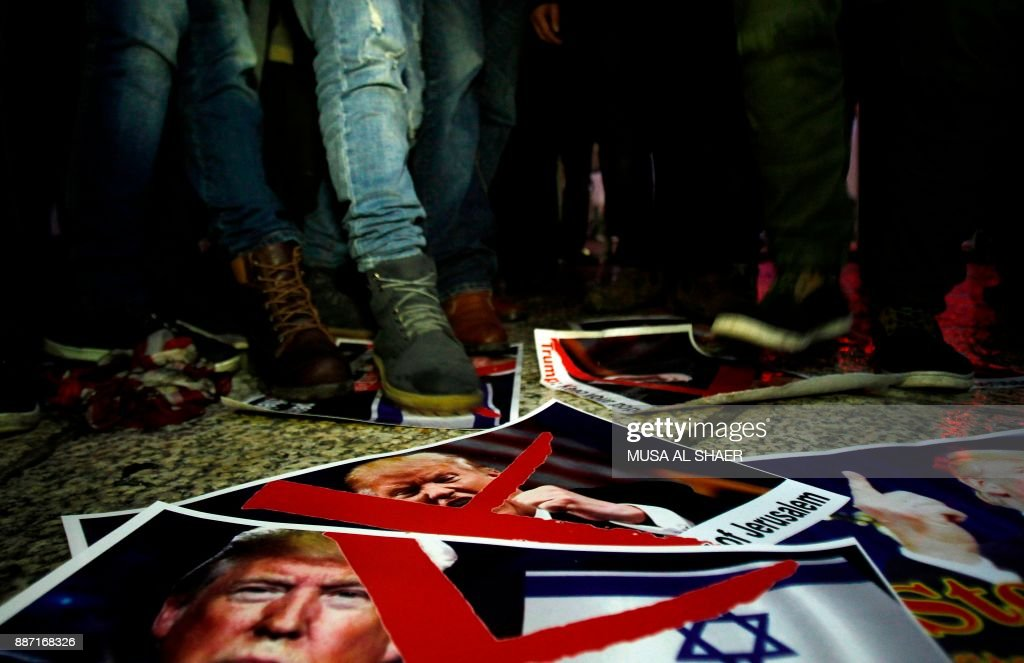 TOPSHOT - Palestinian demonstrators stand on posters of the US president in Bethlehem's Manger Square in protest to him declaring Jerusalem as Israel's capital on December 6, 2017. Abbas said the United States can no longer play the role of peace broker after Donald Trump's decision on Wednesday to recognise Jerusalem as Israel's capital. / AFP PHOTO / Musa AL