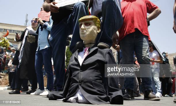 Palestinian demonstrators step on an effigy of US President Donald Trump during a protest against the US-sponsored Middle East economic conference...