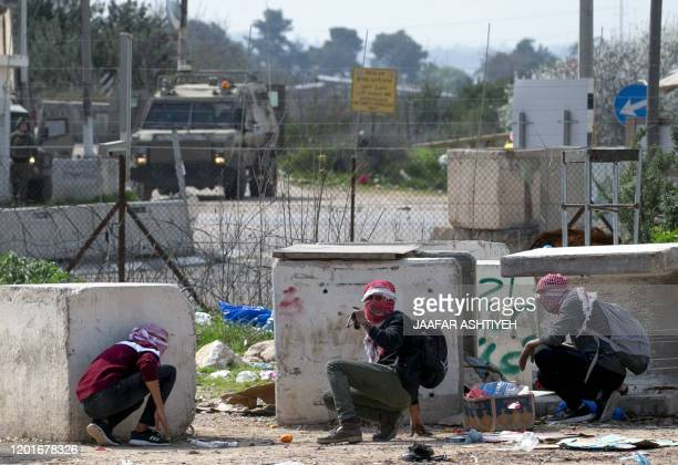 Palestinian demonstrators take cover behind cement blocks amid clashes with Israeli soldiers at the western entrance of the northern West Bank city...