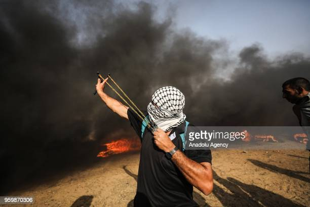 Palestinian demonstrators throw rocks with slingshots in response to Israeli forces' intervention as they burn tyres during a protest within the...