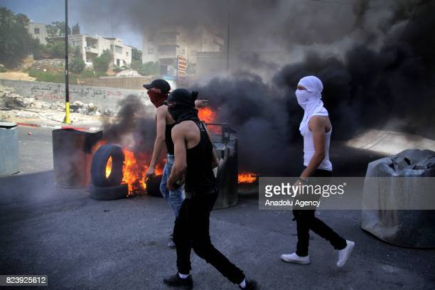 Palestinian demonstrators throw stones and burn tyres in response to Israeli security forces' intervention with tear gas bombs and plastic bullets...
