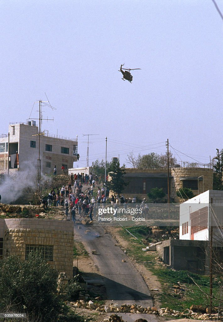 Palestinian demonstrators throw stones at Israeli soldiers during a protest in the streets of Beit Omar. Violence broke out after rebel Israeli and Palestinian fighters protested in the disputed territory of West Bank during the first Intifada. | Location: Beit Omar, West Bank.