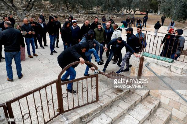 Palestinian demonstrators try to break the lock on a gate at the Al Aqsa mosque compound in Jerusalem's Old City on February 18 after it was closed...