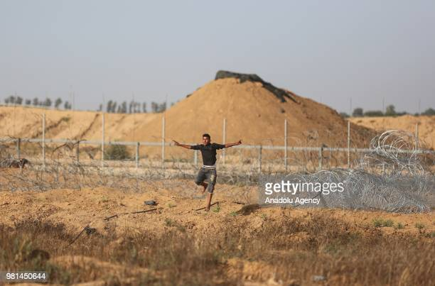 Palestinian demonstrators use slingshots to throw rock in response to Israeli security forces' intervention during a demonstration held within the...