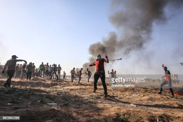 Palestinian demonstrators use slingshots to throw rocks and burn tires in response to Israeli security forces' intervention during a demonstration...