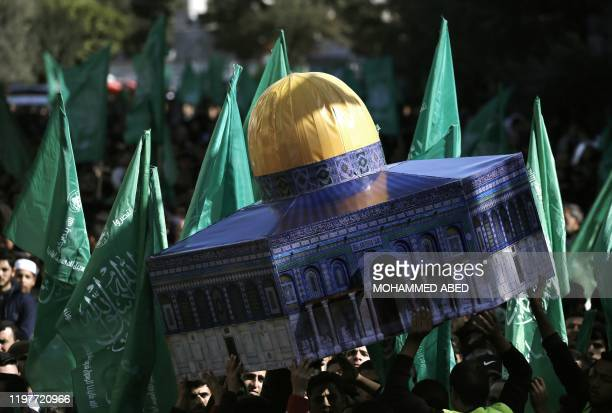 Palestinian demonstrators wave Hamas movement flags and a replica of Jerusalem's Dome of the Rock mosque during a protest in Gaza's Jabalia refugee...