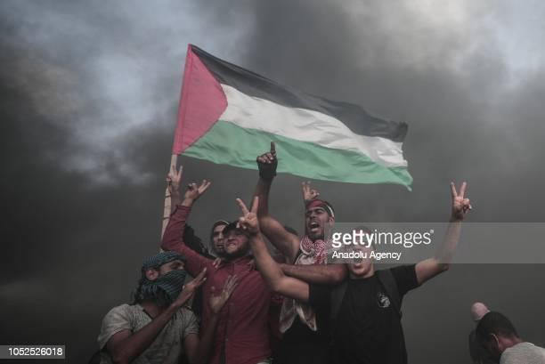 Palestinian demonstrators wave Palestinian flag during the Great March of Return demonstration near IsraelGaza border in Khan Yunis Gaza on October...