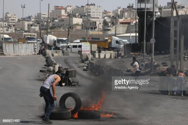 Palestinian demonstrators who stage a demonstration in support of Palestinian prisoners held in Israeli jails throw rocks and burn tires in response...