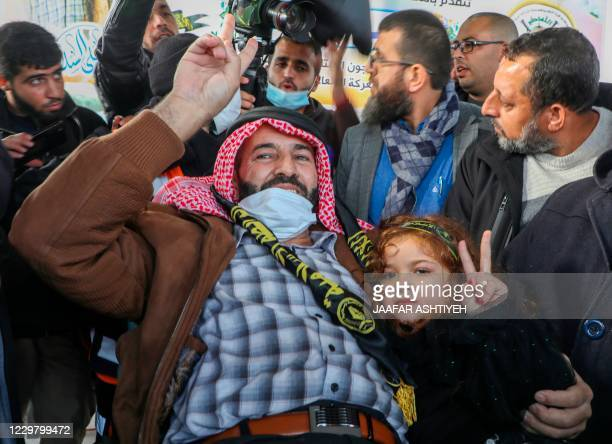 Palestinian detainee Maher alAkhras flashes the V for victory sign with his daughter as arrives at his home in the West Bank village of Seylat...